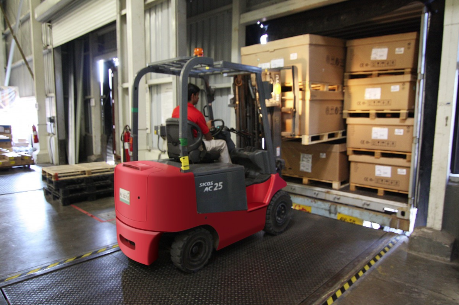 red forklift loading a freight truck bed