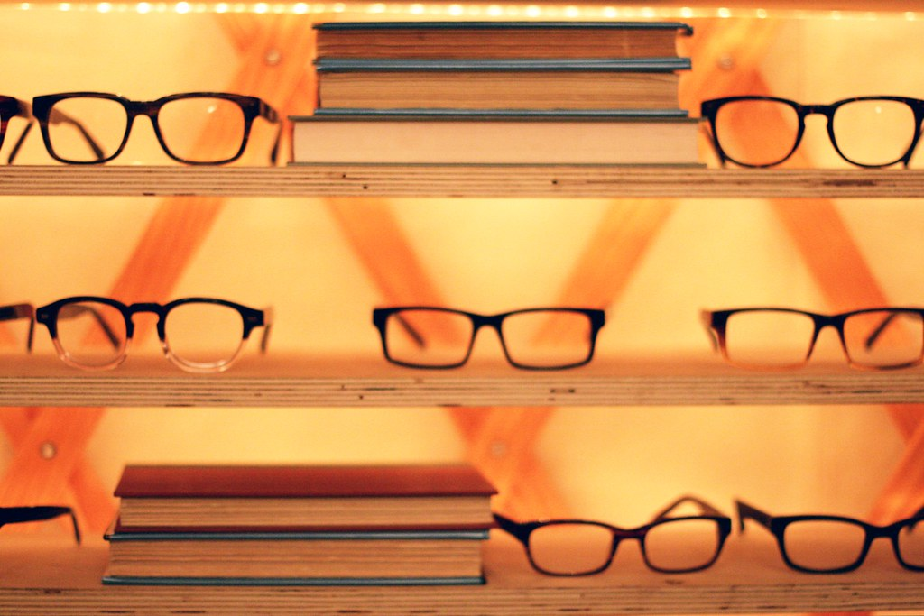 reading glasses on a shelf with stacks of books with an orange background