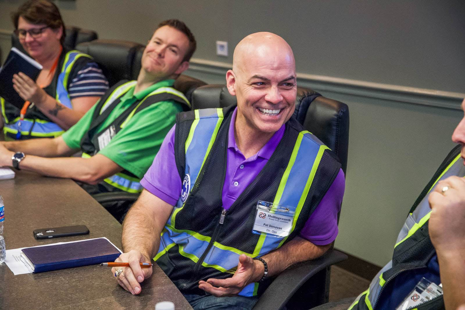 Smiling employees sit at a conference table together