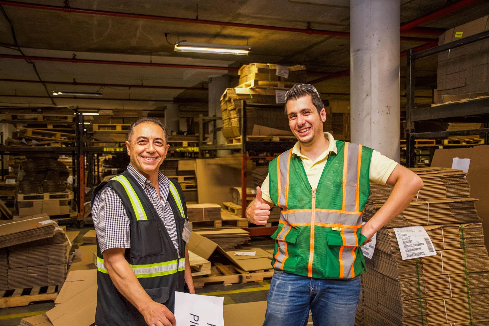 Smiling warehouse employees give a thumbs up