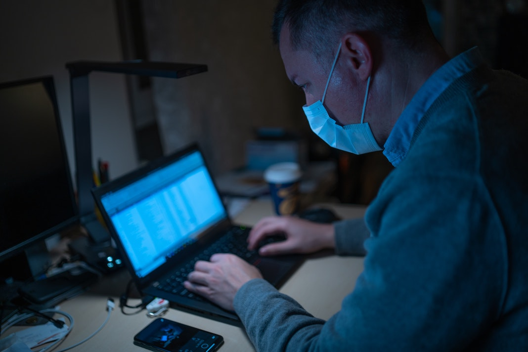 man wearing mask working at desk on laptop